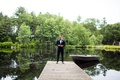 wedding portrait of groom standing at end of dock cedar lakes estate row boat new york