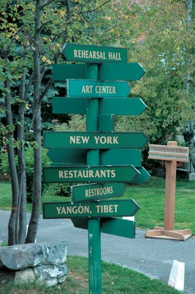 Green sign post with arrows pointing toward different cities