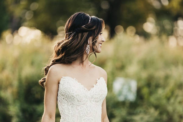 brunette bride with soft waves and delicate bridal halo wearing lace gown with sweetheart neckline