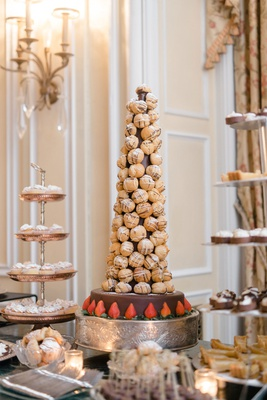 wedding dessert table croquembouche on top of chocolate layer with strawberries pastry stand tiers