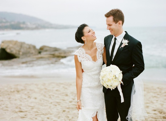Bride and groom laughing while walking on beach
