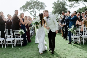 outdoor destination wedding ceremony hawaii kiss white crepe dress and tuxedo jacket grass lawn kiss