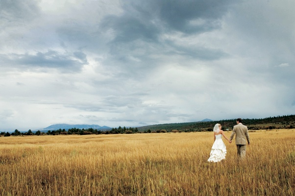 Bride and groom walking in field at ranch in Telluride, Colorado