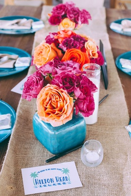 Vibrant wedding decorations on burlap table runner at Hilton Head