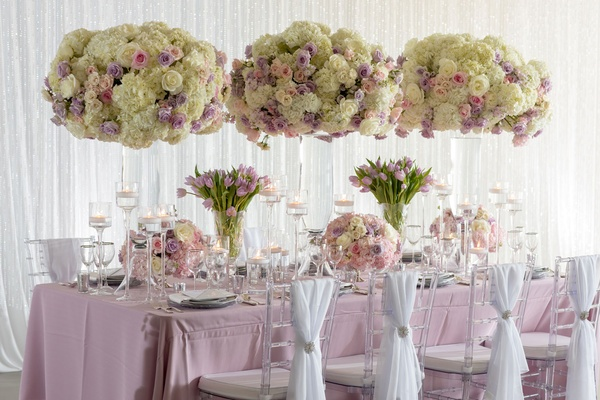 Wedding inspiration reception shoot tall centerpieces clear chairs white sash silver tie back purple