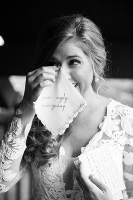 black and white photo of bride dabbing eyes with handkerchief with no ugly crying embroidery