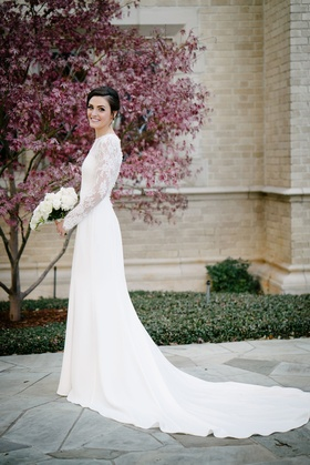 Bride in long sleeve illusion lace wedding dress holding white bouquet for new year's eve wedding