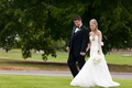 Bride in a strapless fit-and-flare wedding gown walks with groom in a black tuxedo