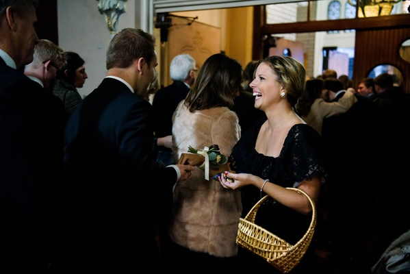 Wedding ceremony church Chicago winter wedding attendant handing our bells to ring at i do ceremony