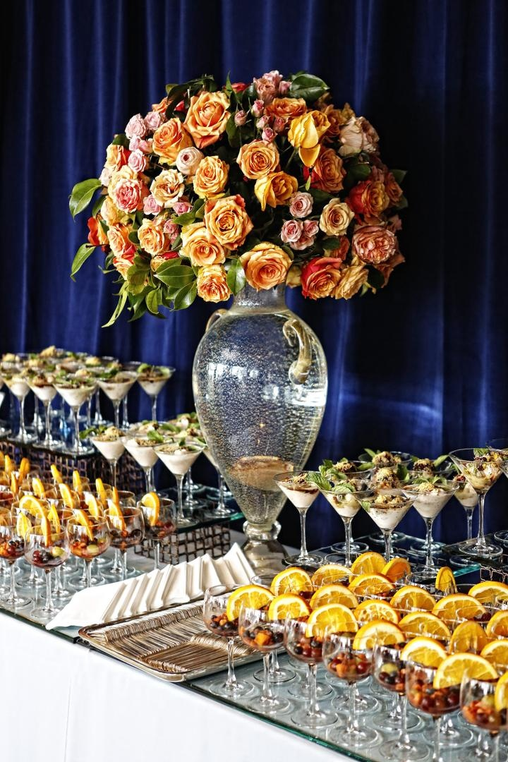 Wedding dessert table with desserts in stemware and floral arrangement of orange and pink roses
