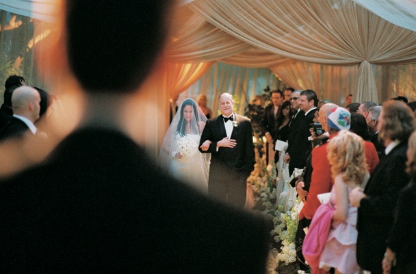 Bride in veil and a strapless gown is walked down the aisle by her father in a tuxedo