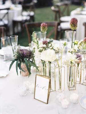 gold bud vases with unique flowers at wedding table