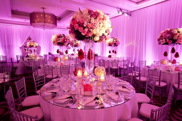 Ballroom wedding with hot pink lighting and large flower arrangements