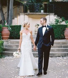 a bride in a soft trumpet wedding gown holding hands with her groom in classic black tuxedo outside