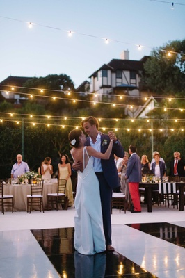 couple dances under fairy lights black white dance floor oceanside california beach wedding
