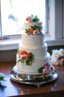 white four tier cake blush icing flowers greenery layered ribboned