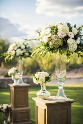 Desert wedding ceremony with oak riser pedestal glass vases white hydrangea, pink rose, greenery