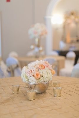 Wedding reception table with ivory hydrangeas, roses, pink dahlias, roses, light orange ranunculus
