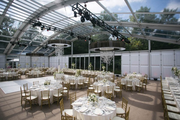 Wedding reception tables under glass arch with sky views