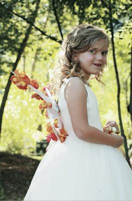 Flower girl in sleeveless white dress with wings
