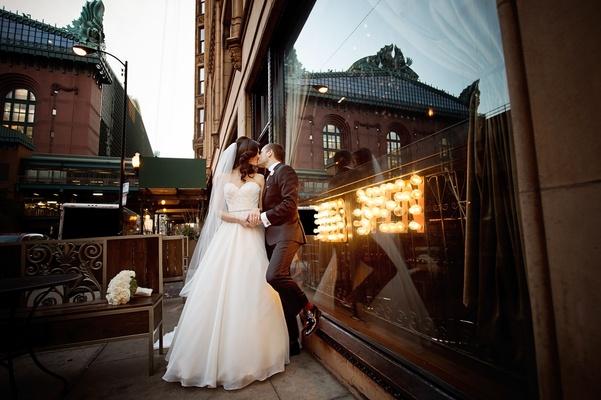 bride in essence of australia wedding dress, groom in bonobos tux, kiss leaning against window