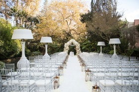 Wedding ceremony outdoors in January Hotel Bel-Air white aisle chairs lanterns heat lamps flowers