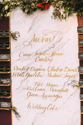 Fall theme wedding reception marble background gold calligraphy menu with marsala wall greenery