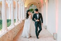 Bride in illusion wedding dress with overskirt long hair pulled to side with groom terrace pathway