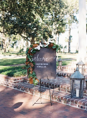 Wood welcome sign with calligraphy wrought iron lanterns on brick stairs magnolia leaves garland
