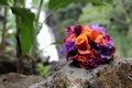 Bridesmaid's bouquet of colorful orange and purple flowers