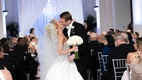 Bride in a strapless Ines Di Santo wedding dress, kisses groom in black tuxedo on ceremony aisle