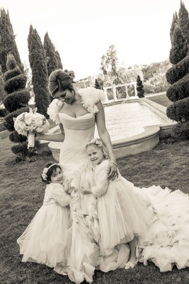 Black and white photo of bride in ruffle dress with flower girls hugging skirt Grand Del Mar