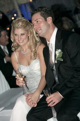 Newlyweds enjoying reception and holding hands
