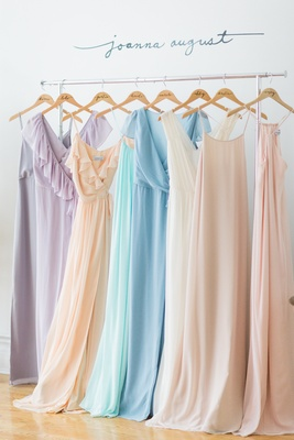 Colorful bridesmaid dresses on clothing rack with personalized hangers by Joanna August 2016
