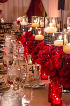 Floating candles and red roses on long tables