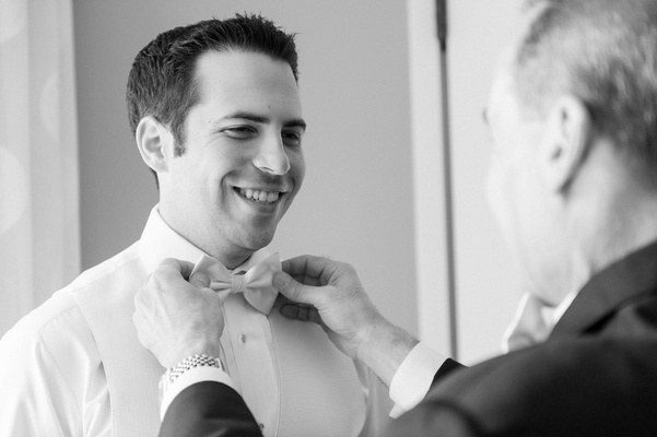 black and white photo of father adjusting groom's bow tie wedding best man florida