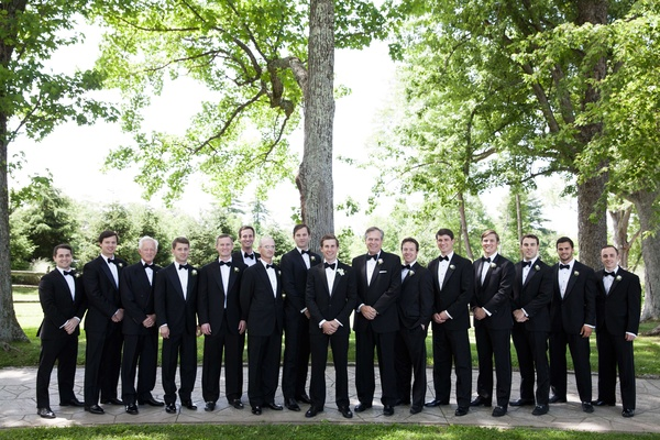 a groom and his groomsmen wearing black tuxedos stand in an open-air area