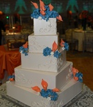 White wedding cake with orange and blue sugar flowers