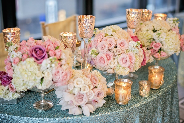Blue sequin tablecloth with gold candle votives and pink flowers