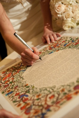 Bride signing colorful Jewish wedding ketubah