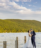 bride in custom hayley paige wedding dress, groom in navy tuxedo, newlyweds kiss on lake dock