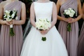 bride in bateau neckline wedding dress white rose bouquet bridesmaids mauve dresses white greenery
