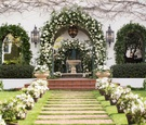 white flowers and greenery on arch of spanish colonial home at home wedding reception ideas