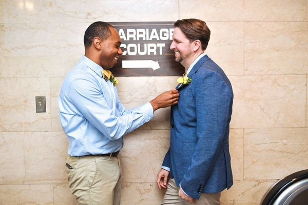 lgbt gay wedding grooms in khaki pants and blue shirt jacket yellow boutonniere marriage court sign