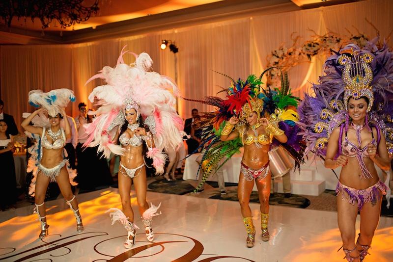 Women in bikinis and large headdresses dancing