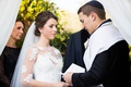 bride and groom with parents under chuppah at ceremony white sheer blouse floral lace groom tallit