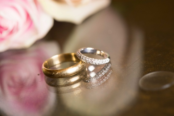 Men's polished gold wedding band and bride's eternity band wedding ring with diamonds