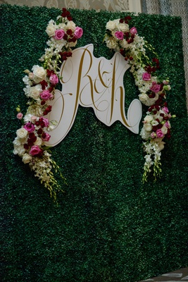 Gold monogram on white border hedge wall greenery backdrop photo booth pink white burgundy flowers