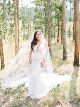 bride in pnina tornai wedding dress with lace cutouts and inserts, cathedral veil in woods