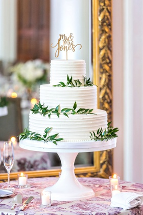 Simple three layer wedding cake with white frosting greenery gold cake topper calligraphy leaves